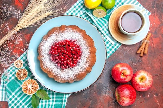 上のクローズアップビューケーキテーブルクロスにお茶シナモンアップルケーキ柑橘系の果物のカップ