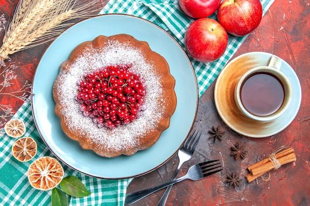 上部のクローズアップビューケーキ一杯のお茶シナモンスターアニスフォークテーブルクロス上のケーキりんご