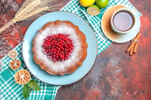 上部のクローズアップビューケーキ一杯のお茶シナモンがテーブルクロスにケーキの柑橘系の果物を貼り付けます