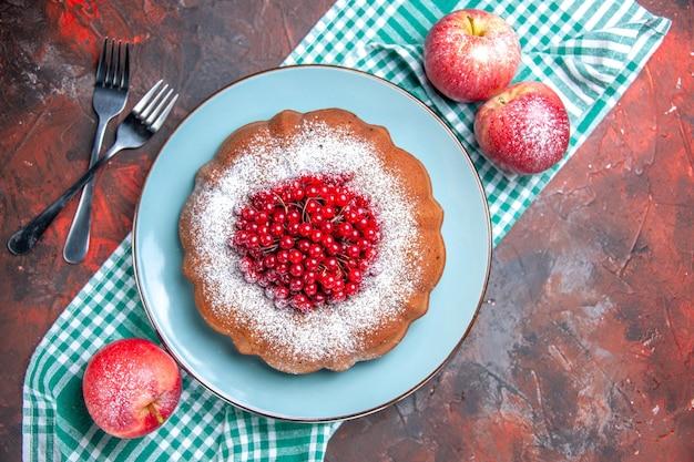 上部のクローズアップは、白青のテーブルクロスのフォークにケーキの食欲をそそるケーキ赤いリンゴを表示します