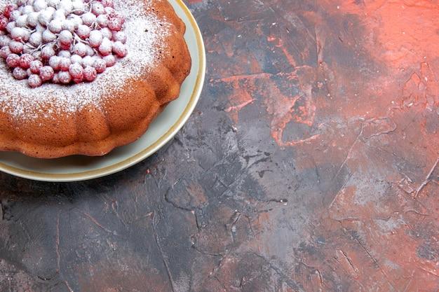 빨간색-파란색 테이블에 붉은 건포도가 있는 식욕을 돋우는 케이크 케이크