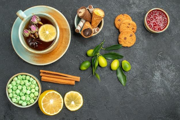 Вид сверху крупным планом чашка чая чашка чая конфеты лимон корица джем цитрусовые фрукты печенье