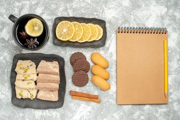 上のクローズアップビュープレート鉛筆ノートにお茶のカップティーレモンのお菓子