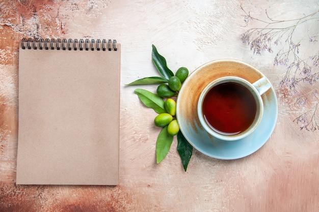 Вид сверху крупным планом чашка чая чашка чая на блюдце цитрусовые фрукты крем блокнот