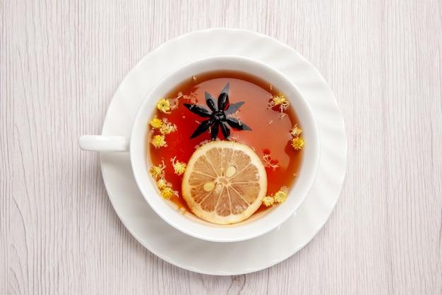 上のクローズアップビュー木製の白いテーブルの上の白い受け皿にレモンのスライスとお茶のカップ
