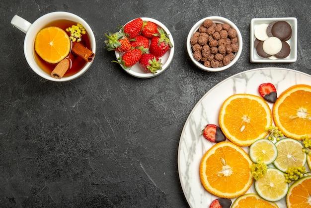 上のクローズアップビューチョコレートイチゴとハイゼルナッツのボウルの横にある柑橘系の果物とイチゴのお茶の食欲をそそる料理とレモンとお茶のカップ