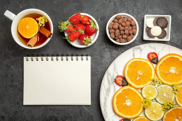 上のクローズアップビューチョコレートイチゴとハイゼルナッツの白いノートのボウルの横にある柑橘系の果物とイチゴのお茶の食欲をそそる料理とレモンとお茶のカップ