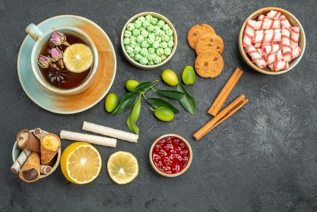 Вид сверху крупным планом чашка чая, печенье, чашка чая, красочные конфеты, варенье, лимон, корица