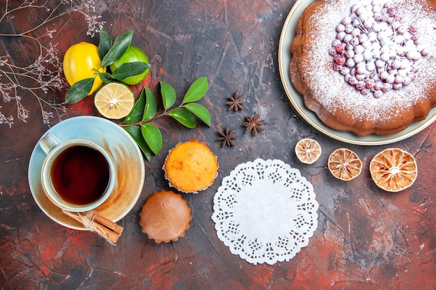 상위 클로즈업 보기 차 컵케이크 한 잔 차 한 잔 계피 레이스 냅킨 감귤류 과일 케이크