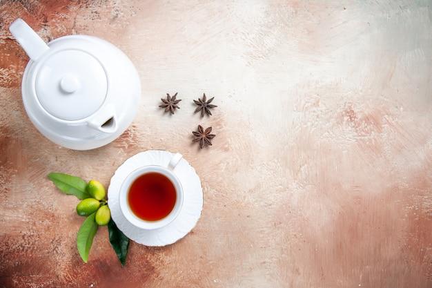 上のクローズアップビューお茶の白いティーポットのカップお茶の柑橘系の果物のスターアニスのカップ
