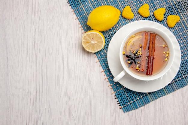 Вид сверху крупным планом чашка чая с корицей чашка чая с лимоном и палочками корицы лимонные конфеты на сине-белой скатерти