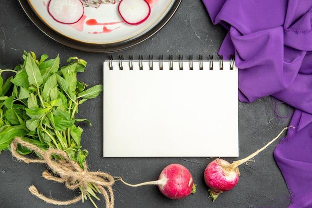 상위 클로즈업 보기 보라색 식탁보에 있는 식욕을 돋우는 무 공책 허브 요리
