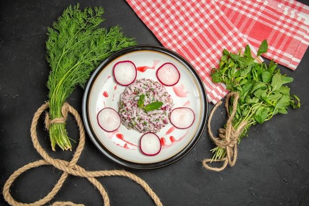 上部のクローズアップは、ロープと市松模様のテーブルクロスで赤みがかった緑の食欲をそそる料理を表示します