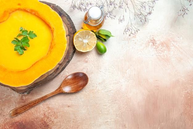 上のクローズアップビューオイルレモンのボードスプーンボトルにハーブとスープカボチャスープ