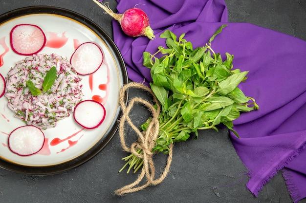 보라색 식탁보 옆에 있는 접시에 있는 식욕을 돋우는 요리 허브 무 소스를 클로즈업으로 봅니다.