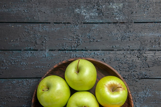 Vista ravvicinata dall'alto mele appetitose sette mele verde-gialle nel piatto sulla superficie scura