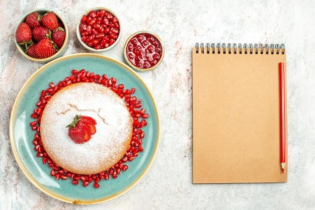 上のクローズアップビュー食欲をそそるケーキイチゴとザクロのボウルの横にザクロと食欲をそそるケーキとテーブルの上の赤鉛筆でクリーム色のノート