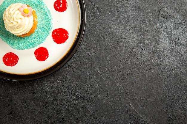 어두운 탁자에 있는 흰색 접시에 다채로운 소스를 곁들인 식욕을 돋우는 컵케이크