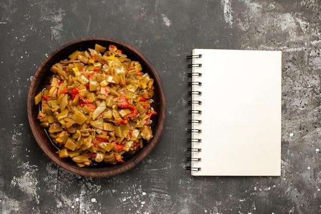 上のクローズアップビュー食欲をそそる皿暗いテーブルの上の白いノートの横にあるサヤインゲンの食欲をそそる料理