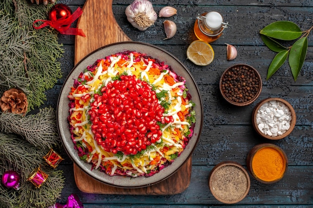 Vista ravvicinata dall'alto piatto appetitoso piatto appetitoso a bordo accanto alle ciotole di rami di spezie con coni aglio olio limone