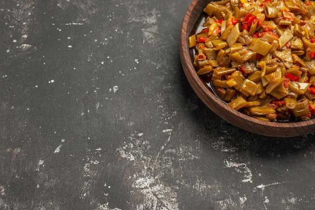 어두운 탁자에 있는 그릇에 녹색 콩과 토마토의 식욕을 돋우는 요리를 가장 가까이에서 볼 수 있습니다.