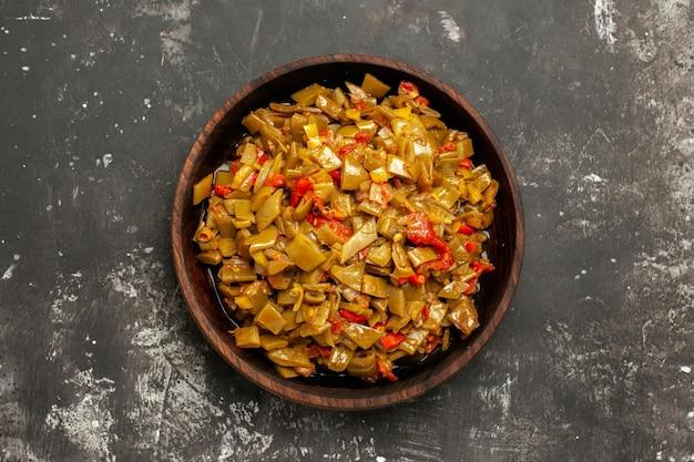 어두운 탁자에 있는 녹색 콩의 식욕을 돋우는 요리를 가장 가까이에서 볼 수 있습니다.