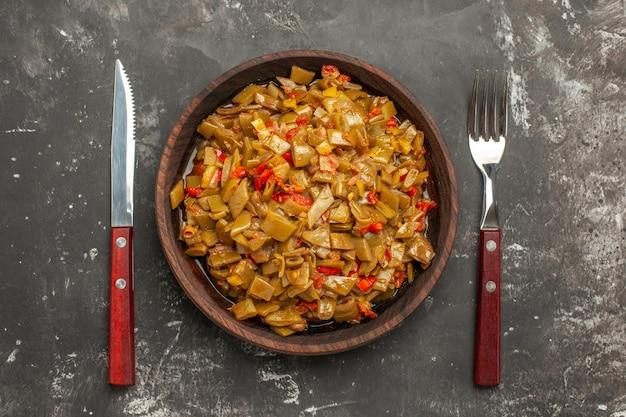 暗いテーブルの上のフォークとナイフの間にトマトとサヤインゲンの食欲をそそる料理の上部のクローズアップビュー食欲をそそる料理