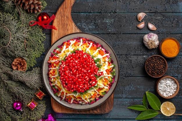 Вид сверху крупным планом аппетитное блюдо на разделочной доске рядом с мисками со специями, ветками с шишками, чесночным маслом, лимоном