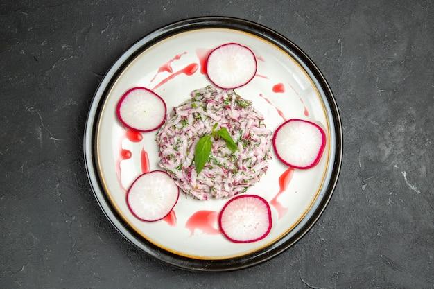 Vista ravvicinata dall'alto di un appetitoso piatto di ravanelli ed erbe aromatiche con salsa rossa