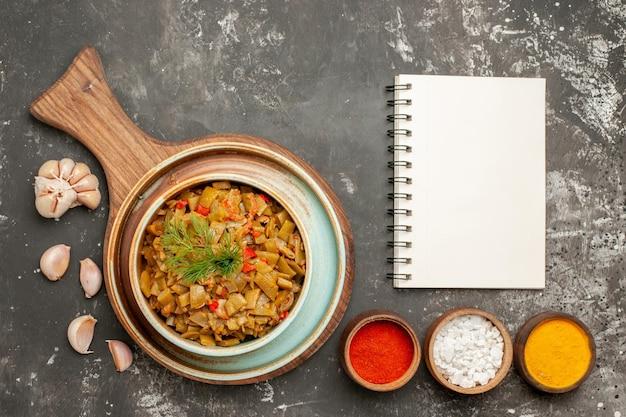 Vista ravvicinata dall'alto fagiolini appetitosi fagiolini e pomodori appetitosi sulla tavola di legno ciotole di spezie aglio e quaderno bianco