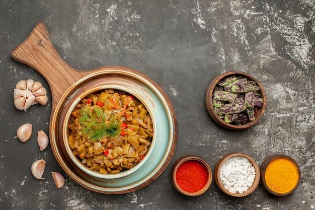 Vista ravvicinata dall'alto fagiolini appetitosi fagiolini e pomodori appetitosi sulla tavola di legno ciotole di spezie fagiolini e aglio