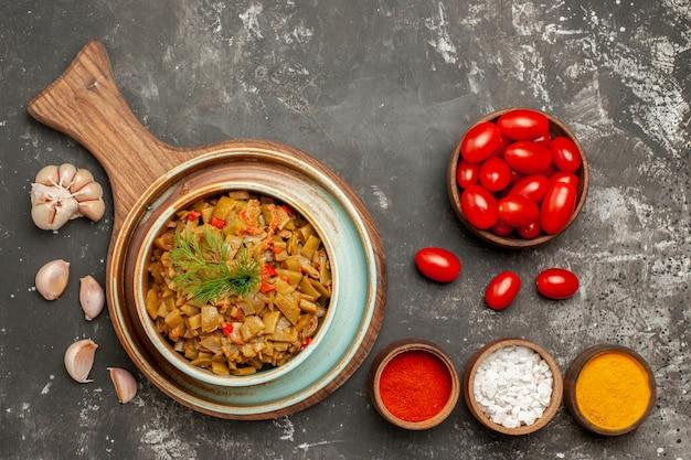 Vista ravvicinata dall'alto fagiolini appetitosi fagiolini e pomodori appetitosi sulla tavola di legno ciotole di spezie pomodori e aglio