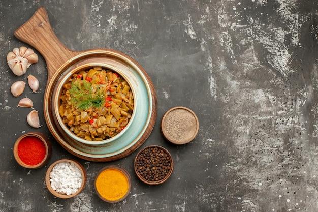 Vista ravvicinata dall'alto appetitoso piatto di fagiolini degli appetitosi fagiolini e pomodori sulla tavola di legno ciotole di spezie aglio sul tavolo scuro