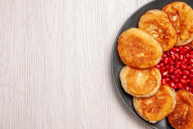 흰색 탁자에 있는 접시에 석류 씨앗이 있는 식욕을 돋우는 팬케이크