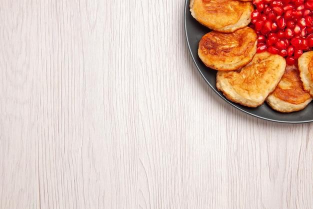 테이블에 석류 씨앗이 있는 식욕을 돋우는 팬케이크의 식욕을 돋우는 팬케이크 블랙 플레이트