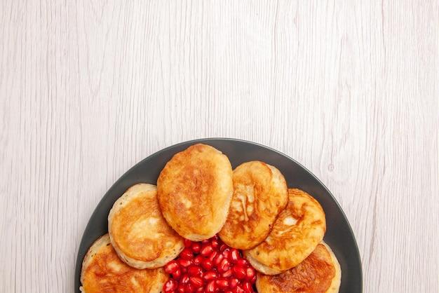 Вид сверху крупным планом аппетитные блины тарелка аппетитных блинов с семенами граната на белом столе