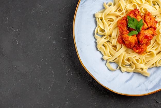 暗いテーブルの上に肉と肉汁が入った食欲をそそるパスタを食欲をそそるトップのクローズアップビュー