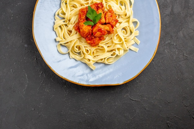 Top close-up view appetizing pasta appetizing pasta with meat on the dark table