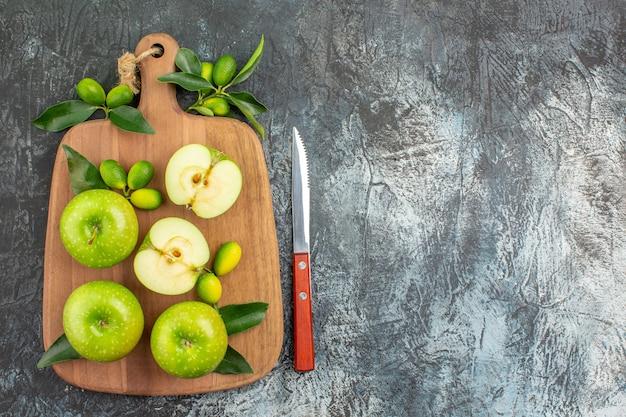 木の板のナイフの上のクローズアップビューリンゴリンゴと柑橘系の果物