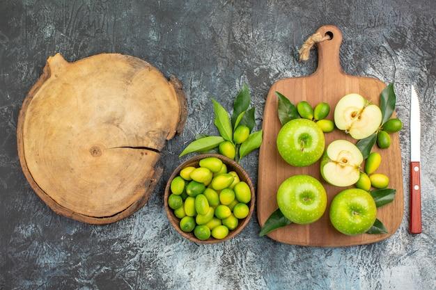 Вид сверху крупным планом яблоки яблоки с листьями нож миска цитрусовых на разделочной доске