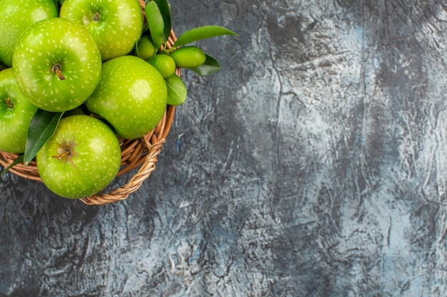 Top close-up view apples basket of green apples with leaves citrus fruits