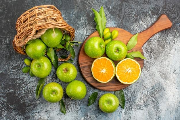 まな板の上に葉の柑橘系の果物とリンゴの上部のクローズアップビューリンゴのバスケット