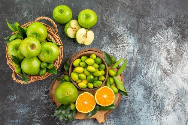 柑橘系の果物の上部のクローズアップビューりんごバスケットは、さまざまな柑橘系の果物とボードをりんご