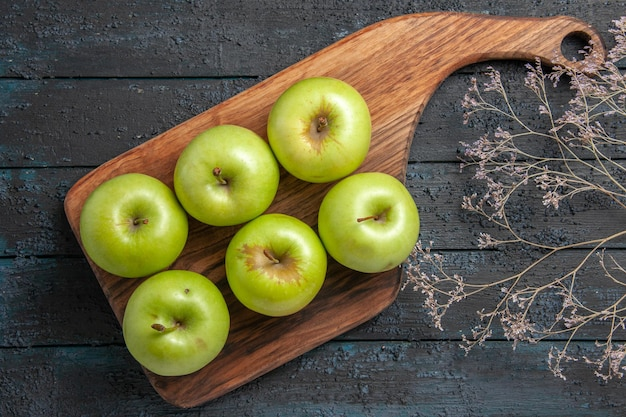 Vista ravvicinata dall'alto mele a bordo di sei mele verdi sulla tavola della cucina accanto ai rami degli alberi su superficie scura