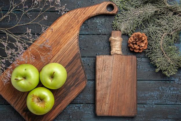 Vista ravvicinata dall'alto mele a bordo tre mele verdi su tavola da cucina e tagliere tra i rami degli alberi con coni sul tavolo scuro