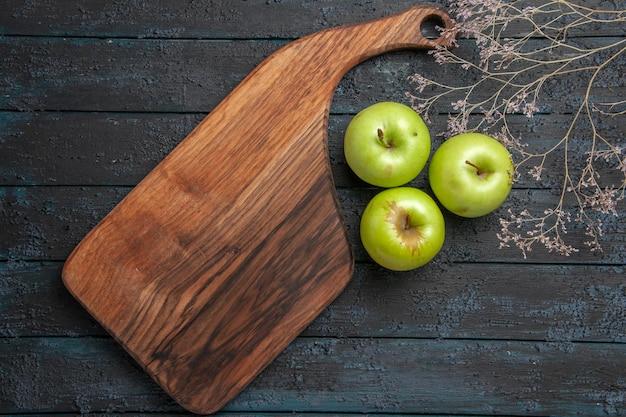 Vista ravvicinata dall'alto mele e bordo di tre mele verdi accanto al bordo della cucina e ai rami degli alberi su una superficie scura