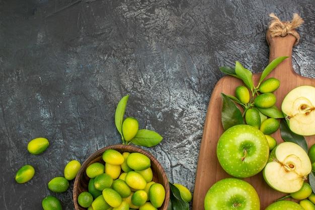 ボード上に葉を持つ柑橘系の果物の青リンゴの上部のクローズアップビューリンゴボウル