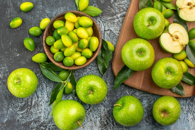 Top close-up view apples citrus fruits board of the appetizing green apples knife