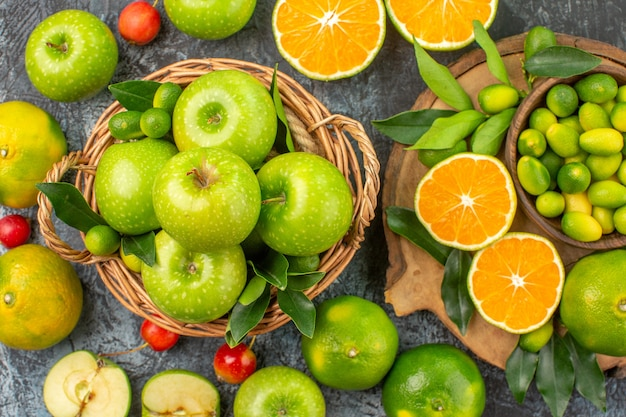Top close-up view apples citrus fruits on the board apples with leaves in the basket cherries