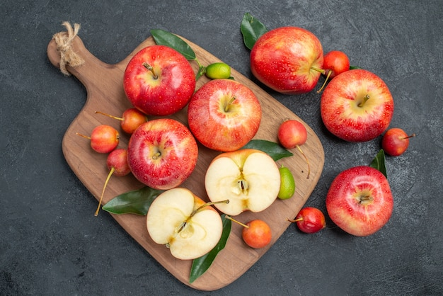 Вид сверху крупным планом яблоки цитрусовые, вишни и яблоки на доске рядом с яблоками